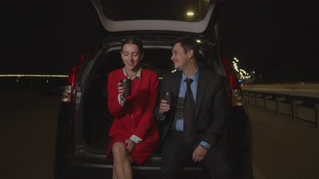 eldobható : Positive attractive businessman serving aromatic refreshing hot drink to cheerful pretty businesswoman, seated in car trunk at night while businesspeople taking a coffee break during business travel.