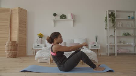 Determined motivated fitness african american woman doing sit-ups on exercise mat at home. Concentrated sporty yogi black female working out sit-ups to strengthen her abdominal muscles indoors.