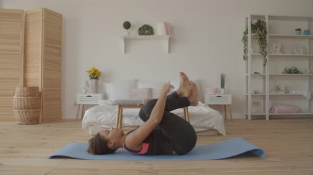 Beautiful sporty fitness african american woman working out on exercise mat, doing knees to chest pose, therapeutic for lower back, to relieve tension in lumbar spine and calm nervous system indoors. Stock mozgókép