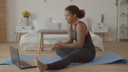 remotely : Positive sporty african american woman consulting with fitness trainer online via laptop while sitting on exercise mat at home. Cheerful female using online personal fitness trainer service on laptop.