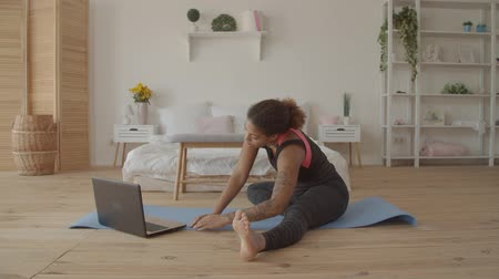 remotely : Determined sporty african american woman working out, doing stretching exercise on yoga mat while watching fitness video online on laptop at home. Female practicing yoga exercise online with laptop pc