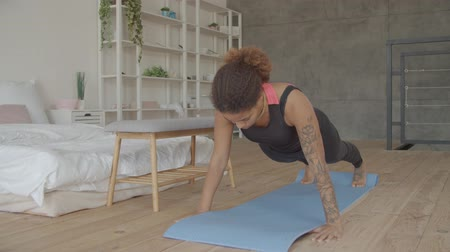 planking : Motivated determined sporty fit african american woman on fitness mat doing plank static exercise for abdominal strength in domestic room. Concentrated female practicing pilates plank exercise indoors