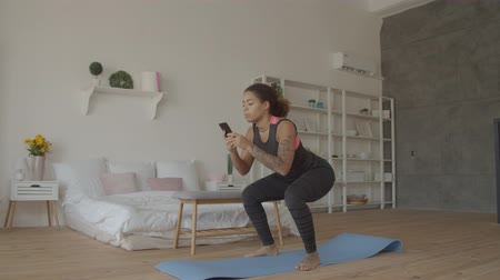 Multitasking sporty fitness african american woman doing squats and browsing online on smart phone in loft apartment. Busy with cellphone fit attractive black female working out and squatting at home.