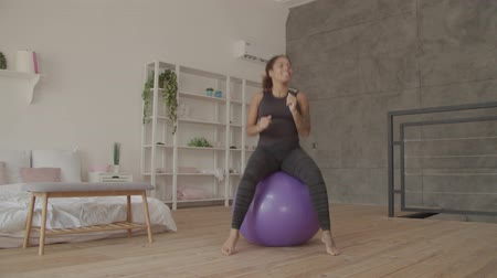 Cheerful smiling young african american woman in sportswear sitting and jumping on fitball in domestic room during workout. Positive sporty fit female practicing pilates exercise with fitness ball. Stock mozgókép