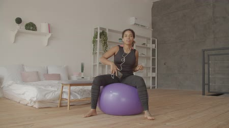Positive sporty african american woman in earphones sitting on fitball, enjoying her favorite music using cellphone after indoor workout, expressing positive vibes, carefree mood and wellness. Stock mozgókép