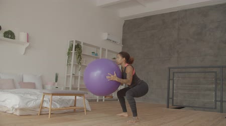 Determined concentrated young black female in sports clothes practicing squats with fitness ball in domestic interior. Motivated sporty fit woman crouching with fitball during indoor workout. 動画素材
