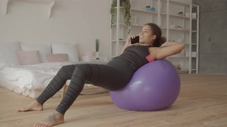 Relaxed beautiful african american woman in sportswear lying comfortably on fitball and chatting on smartphone after indoor workout. Cheerful sporty female talking on cellphone after fitness training. Stock mozgókép