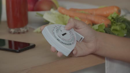 Close-up of female hand using body mass index or BMI calculator, measuring the relative weight based on an individuals mass and height at kitchen table with fresh healthy food in background. 動画素材
