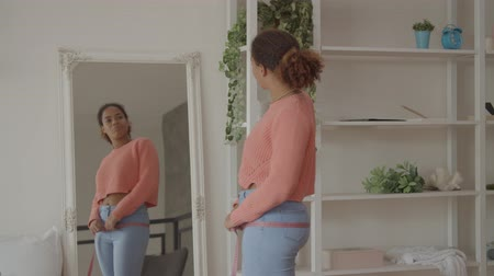 Smiling african american female in casual clothes with perfect body shape measuring her hips with measuring tape, standing in front of mirror, expressing positivity with successful weightloss program. 動画素材