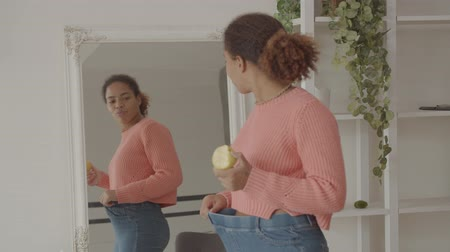 Joyful confident african american woman in loose old pants eating apple, admiring her appearance and perfect body shape in mirror after successful weightloss in domestic room, being excited and proud.