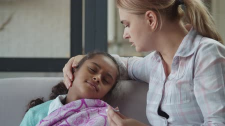 Upset loving caucasian mother holding digital thermometer, caressing and comforting her ill cute preadolescent mixed race daugther with high fever in domestic room, expressing love, support and care.
