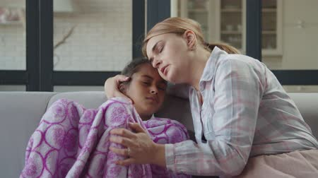 concern : Pretty loving caring mother embracing, caressing and comforting upset unwell preadolescent cute mixed race daughter, covered with blanket, on sofa in domestic room, expressing love, care and support