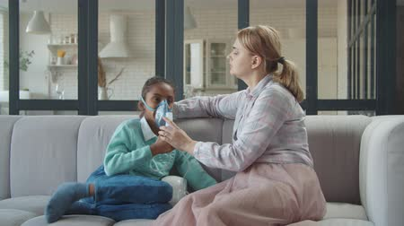asthma : Caring affectionate mother helping to cute preadolescent mixed race daughter with nebulizer mask in domestic room, applying medicine inhalation treatment on girl with asthma by jet nebulizer..