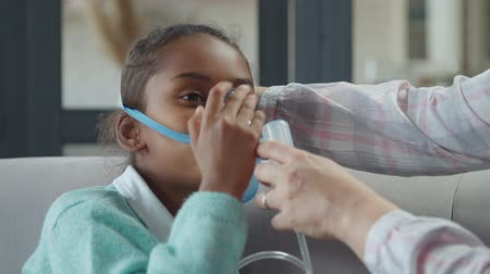 therapeutic : Close-up of caring mothers hands helping to ill adorable preadolescent mixed race daughter to apply nebulizer mask at home. Sad sick child making inhalation therapy using jet nebulizer indoors. Stock Footage