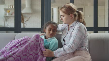 Cute mixed race preadolescent sick girl with fever heat feeling cold and unwell while caring lovely mother covering kid with warm blanket and comforting on her lap in domestic room, caressing gently.