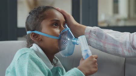 Portrait of sick cute african american preadolescent girl applying medicine inhalation treatment using ultrasonic wave nebulizer at home, inhaling medicine for asthma while mom gently caressing her. Stock mozgókép