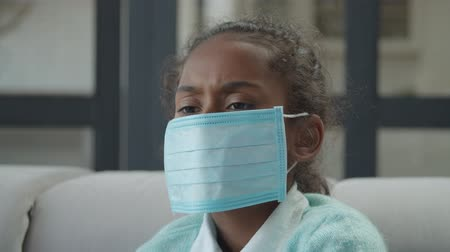 influenza : Portrait of unhealthy sad african american preadolescent girl wearing protective medical mask to prevent the spread of germs at home, suffering from cold and flu, feeling unwell and depressed.
