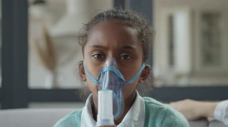 lung : Portrait of beautiful african american elementary age girl doing asthma breathing treatment with nebulizer at home. Sick cute child making inhalation with medical ultrasonic inhaler in domestic room. Stock Footage