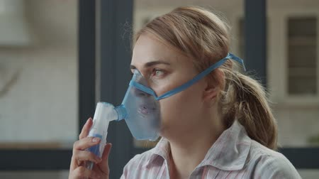 dýchání : Portrait of unwell beautiful adult woman using nebulizer for asthma and respiratory diseases at home. Sick female making medicine inhalation treatment using jet nebulizer in domestic room. Dostupné videozáznamy