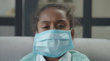 Portrait of unwell elementary age african girl wearing protective medical mask to prevent spread of germs indoors during flu season, feeling unhealthy, looking with eyes full of grief and sadness.