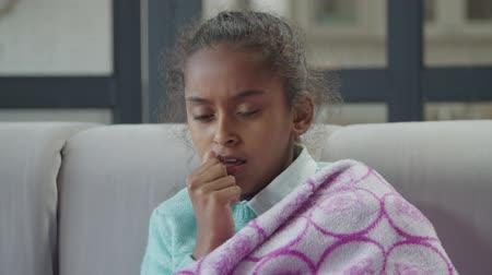 wrapped up : Portrait of cute unwell elementary age african american girl wrapped in warm blanket coughing while resting on sofa at home. Sick child with dry cough, cold and high fever sitting in domestic interior