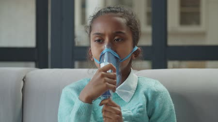 lung : Portrait of asthmatic cute african american elementary age girl intense breathing through nebulizer mask, doing medical procedure for treatment of asthma using therapy apparatus in domestic interior.