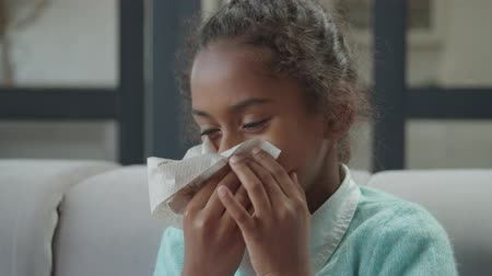 Portrait of adorable elementary age sick african american girl blowing her runny nose into tissue paper at home. Unhealthy child suffering from running nose and sneezing, wiping nose by tissue paper. Stock mozgókép