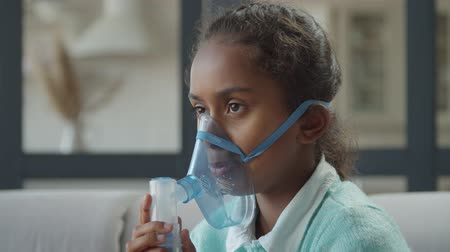 inhalacja : Portrait of sick preadolescent african american girl in nebulizer mask inhaling drugs to treat respiratory diseases in domestic interior. Ill child making inhalation treatment for breathing at home. Wideo