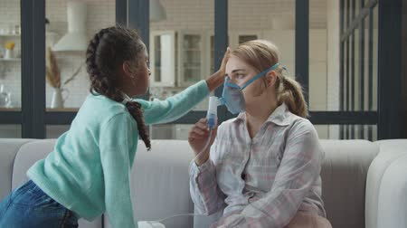 influenza : Loving mixed race elementary age daughter consoling unwell mother in nebulizer mask while making medicine inhalation treatment for respiratory disease in domestic room, expressing support and care.