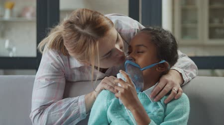 Loving caucasian mother supporting, embracing unwell preadolescent mixed race daughter while making medicine inhalation with jet nebulizer for cough treatment, expressing love and care at home.