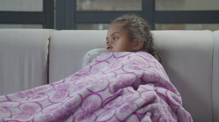 puericultura : Portrait of unwell sad elementary age african girl with influenza and high fever wrapped in warm blanket sitting on sofa in domestic room, looking unhealthy and depressed, feeling chills