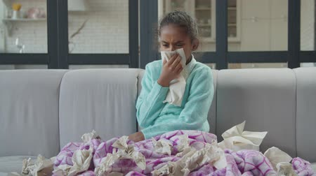 Lovely sick african american elementary age girl covered with warm blanket sitting on sofa, surronded by many used tissues, blowing runny nose in tissue paper in domestic interior during flu season.