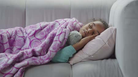 прижиматься : Portrait of cute preteen african american girl hugging teddy bear and sleeping on sofa in domestic room. Tired elementary age child resting on the couch with toy and falling asleep at home.. Стоковые видеозаписи