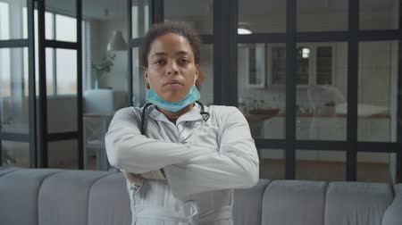 ciddi : Portrait of serious attractive african american female physician with protective medical mask and stethoscope posing with arms crossed in home interior, expressing confidence and determination. Stok Video
