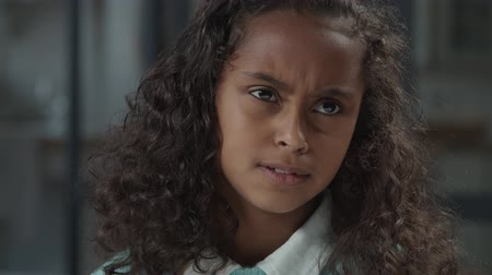 dalgın : Portrait of attractive upset african preteen girl with curly hair almost crying, looking with eyes full of sorrow, sadness and depression, feeling resentment, sulky and hopelessness indoors.