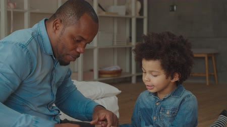pai : Portrait of caring black father helping cute mixed race son to build from colorful plastic construction blocks at home while spending playtime together, developing creativity of preschool child.
