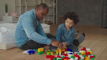 pai : Engaged caring african dad and adorable preschool mixed race curly son building form colorful plastic blocks on floor at home. Multiethnic family playing developing game with constructor indoors.