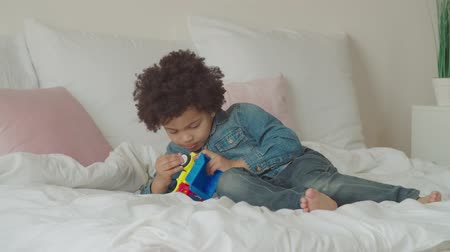 engrossed : Concentrated cute preschool mixed race boy repairing broken toy car while lying on bed at home. Serious engrossed in action little multiethnic kid with curly hair fixing toy in bedroom.