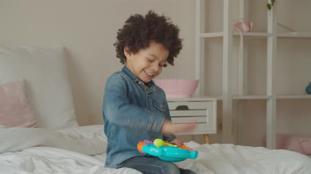 engrossed : Overjoyed engrossed in game cheerful little mixed race boy playing with toy steering wheel on bed in domestic room, pressing car horn, imagining driving car, expressing excitement and carefree mood. Stock Footage
