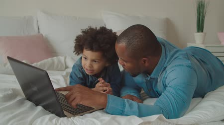surfing the net : Positive caring handsome african father and joyful adorable preschooler mixed race son networking with laptop pc on bed, communicating ,watching online educational and developing programs for kids.