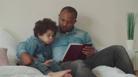 engrossed : Caring loving black daddy embracing adorable preschooler multiethnic boy with curly hair, reading interesting fairy tale together on bed. Positive diverse family with child enjoying leisure at home.