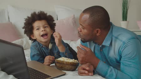 pai : Portrait of joyful carefree black father and smiling adorable preschool mixed race son enjoying leisure together on bed, eating popcorn, watching movie online using laptop pc, bonding during weekend.