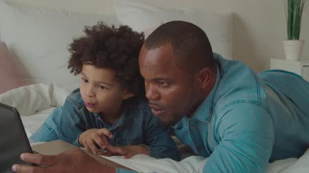 surfing the net : Positive concentrated handsome black father with lovely little mixed race son browsing content online with laptop on bed. Multiethnic family with kid surfing net on laptop pc and e-learning at home. Stock Footage