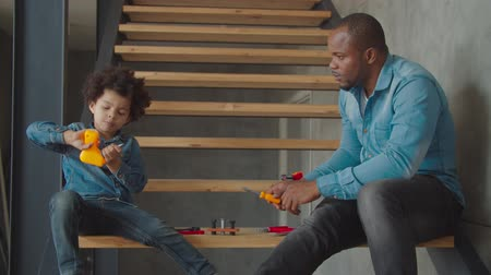 engrossed : Serious fully engrossed in action adorable mixed race preschool boy playing with toy drill and caring father helping son to use properly work tool on stairs at home, developing childs craft skills. Stock Footage