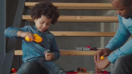 engrossed : Positive focused cute biracial preschool boy with curly hair learning to use work tools by guidance of his black father, using toy drill while sitting on stairs, playing developing game with toy tools