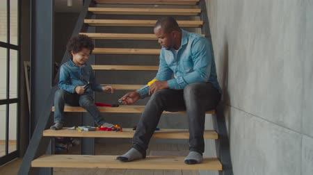trabalhador manual : Positive engrossed in action multiethnic preschool boy and caring black dad playing with toy work tools on stairs. Father teaching little son to use different tools, playing developing game at home.