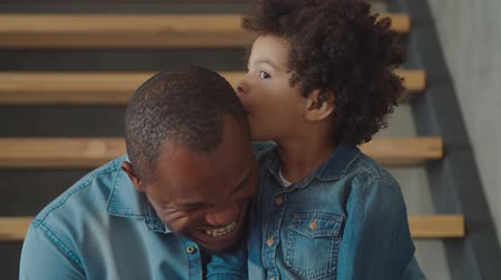 whispering : Cheerful smiling adorable mixed race preschool son whispering gossips, sharing secrets with handsome laughing black father on stairs at home. Trust-based warm relations between daddy and child.