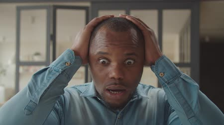 údiv : Indoor portrait of shocked emotionally stressed african man with wide opened mouth and eyes touching head with two hands, looking desperate and disbelieved by bad news. Dostupné videozáznamy