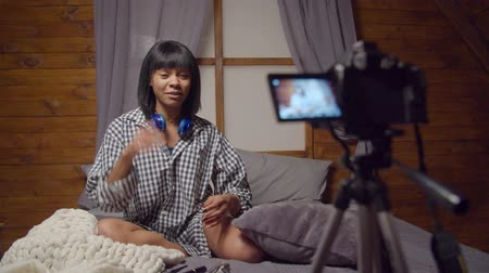 kořist : Laughing african american female vlogger in domestic clothing seated on bed made bloopers during recording video for blog at home. Funny web influencer misspoken words during broadcasting vlog online.