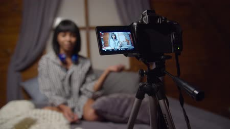 blogger : Positive female vlogger recording her daily video blog on tripod mounted camera in domestic bedroom at night. Focus on camera screen. Web influencer recording message for internet social networks. Stock Footage